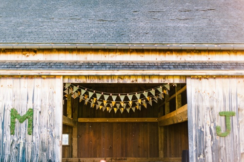 German barn with white and gold pennant flags and moss initials